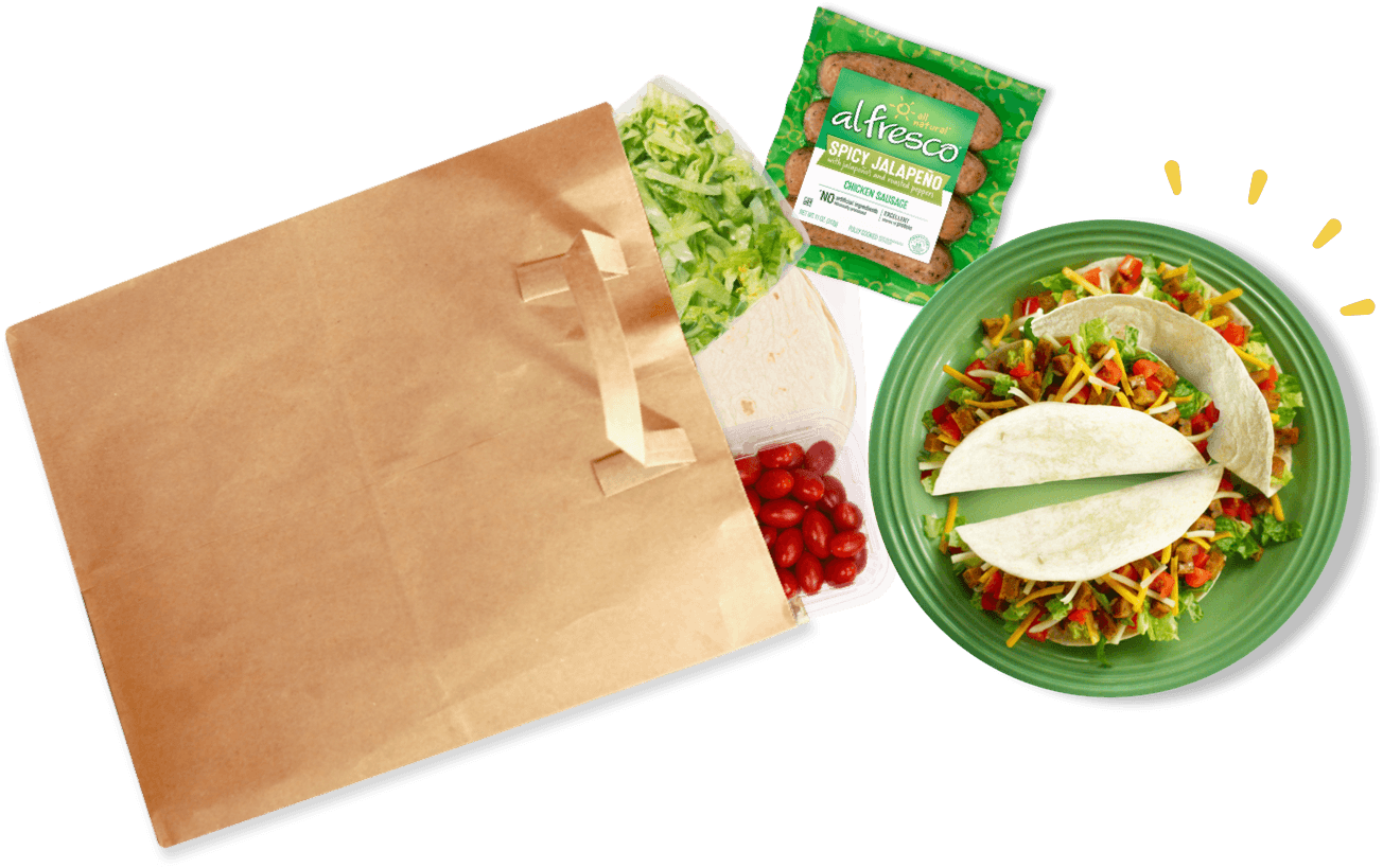Plate of assembled tacos next to a paper bag spilling ingredients.