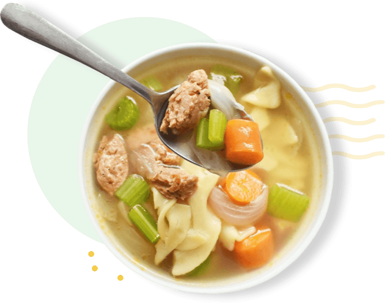 Chicken sausage noodle soup in a bowl with a spoon