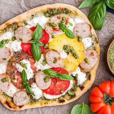 Grilled chicken sausage pesto pizza on a cutting board.