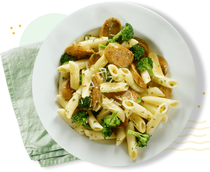 Plate of pasta with broccoli and chicken sausage and folded napkin