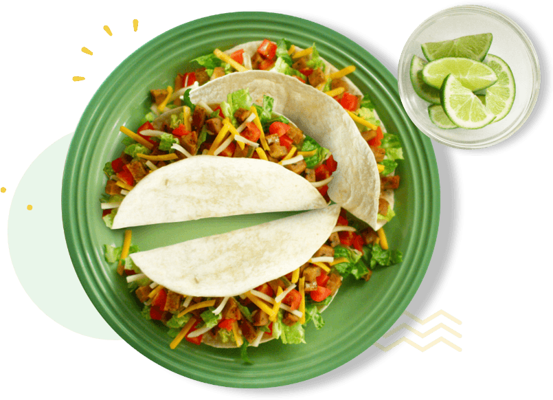 Three tacos served on a plate with a side of cut limes.
